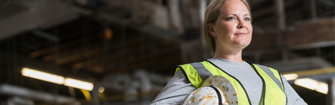 Women in safety work vest holding hard hat